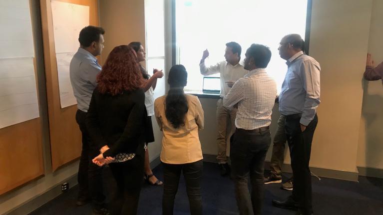 group of staff members in big room planning meeting