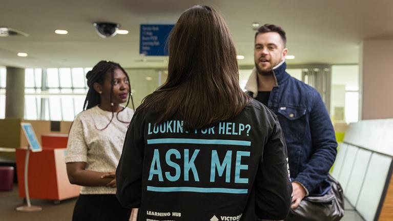 Back of student showing 'Ask me' written on shirt; talking to white male and African-Australian students