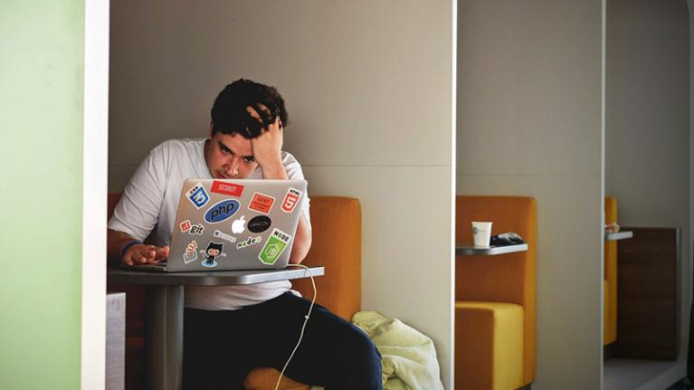 young man looking anxious in front of laptop