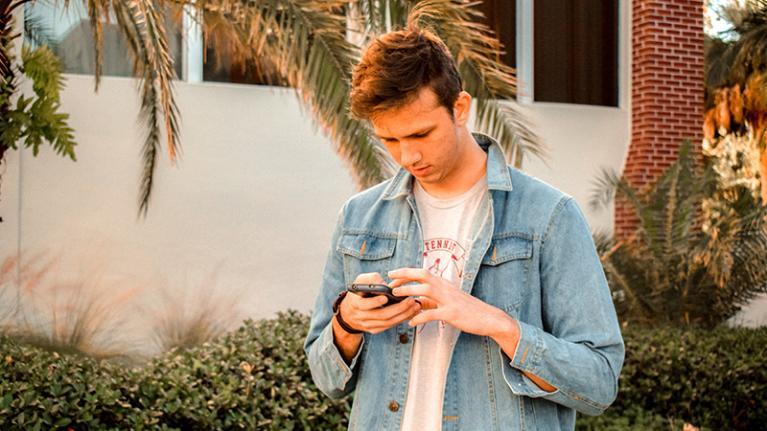 boy walking down street looking at smartphone