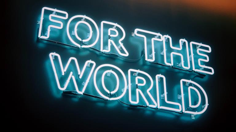 "neon sign with the words ""for the world"""