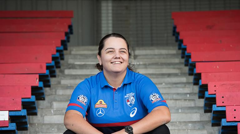 Brooke Muscat in Western Bulldogs uniform sitting on steps in a stadium