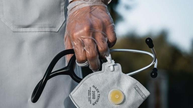 A gloved hand holding a mask and stethoscope