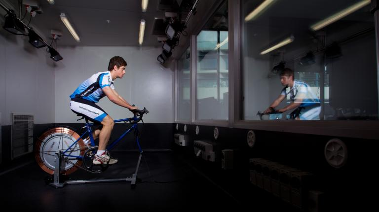 A male-presenting person riding an exercise bike indoors in a gym.