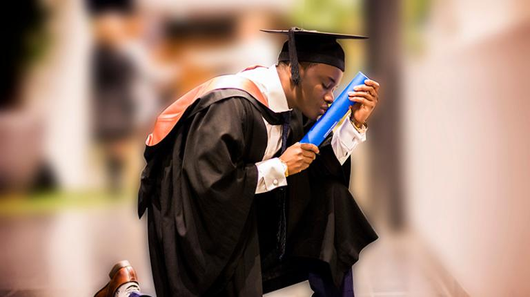 Student kneels to kiss degree