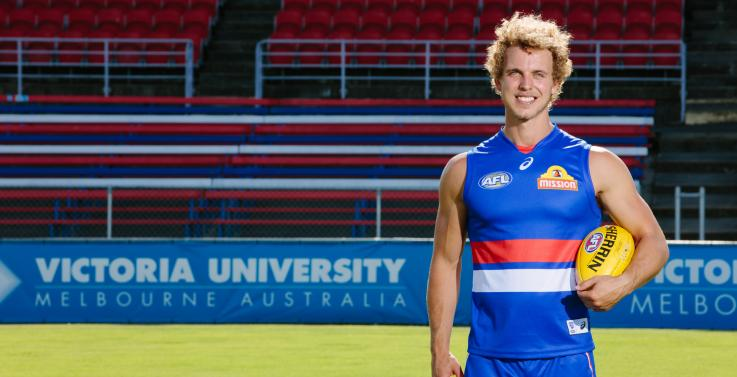 Mitch Wallis in his Bulldogs gear stands in front of a VU banner